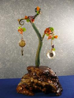 This sculpture is drapped in orange paper flowers with antique watches and a glass heart